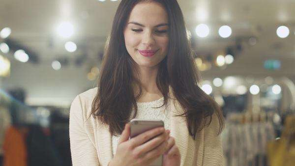 Happy young brunette woman is standing in a department store and using a smartphone. Royalty-free stock video