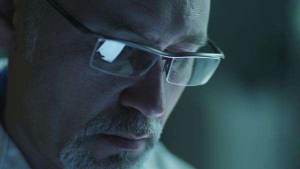 Portrait of middle-aged male using tablet and have reflections of screen in glasses. Close-up Royalty-free stock video