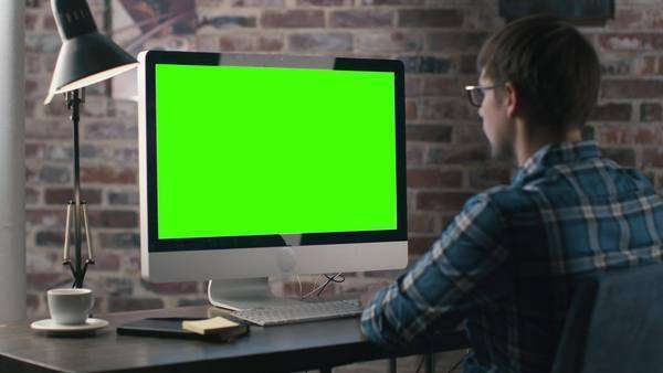 Young man is working on a computer with a mock-up green screen. Royalty-free stock video