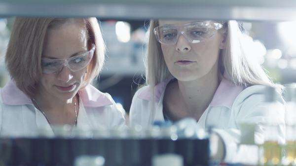 Two female scientists are working with  liquid samples in a tube in a laboratory. Royalty-free stock video