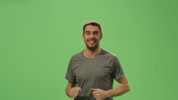 Man in a t-shirt is jogging on a mock-up green screen in the background. Royalty-free stock video