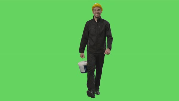 Construction worker in a hard hat holding a bucket with paint is walking on a mock-up green screen in the background. Royalty-free stock video