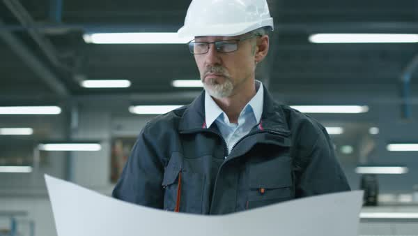 Senior engineer in hardhat is standing in a factory and looking at a blueprint. Royalty-free stock video