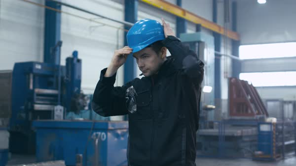 Factory worker in blue uniform is putting his hard hat and goggles on while walking. Royalty-free stock video