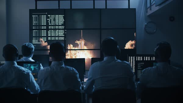 Group of people in mission control center filled with displays, celebrating successful rocket launch. Elements of this image furnished by NASA. Royalty-free stock video