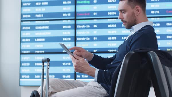 Man using tablet while waiting boarding at departure lounge at the airport. Royalty-free stock video