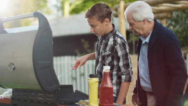Grandfather and Grandon Are Cooking Burgers on Grill at Bright Summer Day. Royalty-free stock video