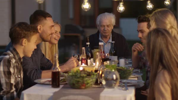 Group of People Sitting Around a Table, Eating, Communicating and Having Fun during Family Dinner. Royalty-free stock video