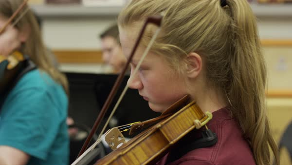 Close up of panning shot of teenage girl playing violin in orchestra  practice stock footage