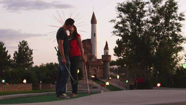 Medium shot of couple kissing standing on golf course at dusk Royalty-free stock video