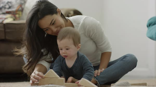 Medium panning shot of mother and son playing with blocks on floor Royalty-free stock video