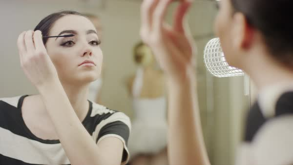 Close up of ballerina applying mascara in mirror Rights-managed stock video
