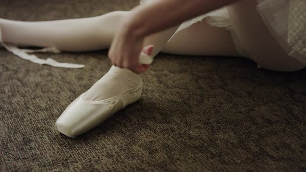 Close up shot of ballerina sitting on floor putting on ballet shoe Rights-managed stock video