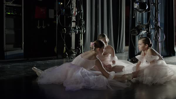 Medium panning shot of ballerinas stretching backstage Rights-managed stock video