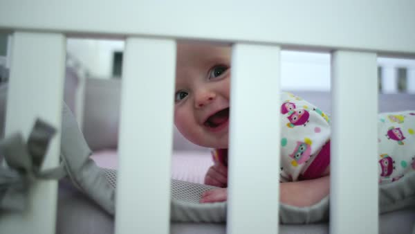 Hand-held close-up of funny playful baby girl in bed Royalty-free stock video