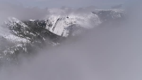 Aerial Flying Through Fog Clouds to Reveal Hazy Snow Covered Mountain Forest Royalty-free stock video