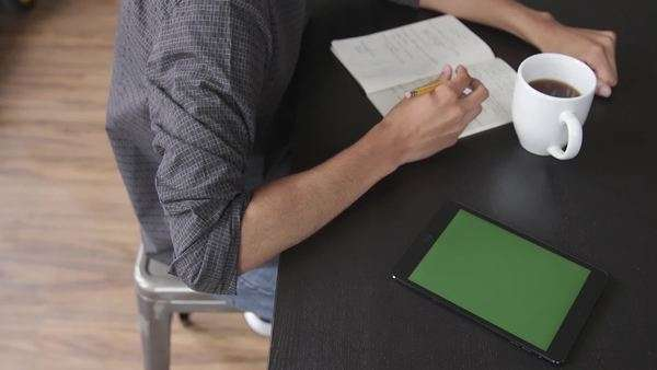 Male writing in notebook with tablet next to him. Royalty-free stock video