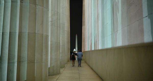 WASHINGTON, D.C. - Circa July, 2015 - Two people walk along side the Lincoln Memorial at night with the Washington Memorial and Capitol Building in the background. Royalty-free stock video