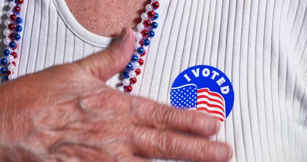 An elderly woman puts an I Voted sticker on her shirt. Royalty-free stock video