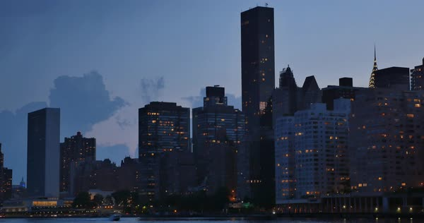 An evening or dusk establishing shot of the midtown Manhattan skyline as seen from Roosevelt Island.	 	 Royalty-free stock video