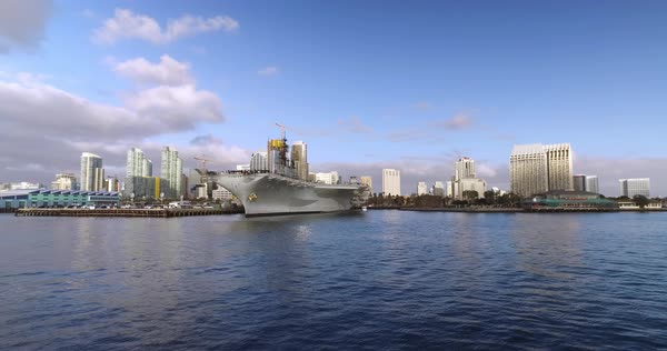 A wide, dramatic daytime establishing shot of the San Diego city skyline as seen from the bay. The USS Midway aircraft carrier museum is in the foreground. Royalty-free stock video