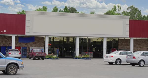 A daytime exterior DX establishing shot of an unbranded, generic grocery store. Blank marquee for customization.   Royalty-free stock video