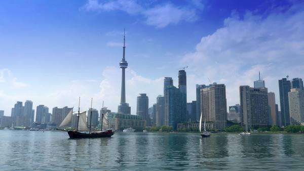 TORONTO, ONTARIO, CANADA - Circa June, 2014 - An establishing shot of Toronto, Canada as seen from a boat on Lake Ontario as tall ships pass by. Royalty-free stock video