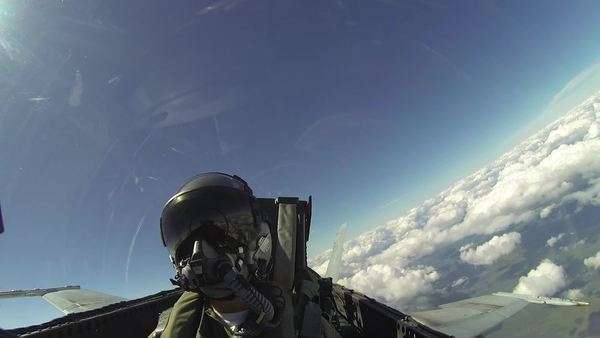 View of F18 fighter plane passenger, or pilot, looking towards their face as plane does maneuvers above cloud line. Royalty-free stock video