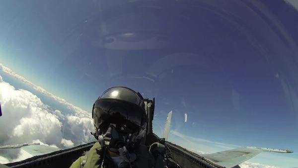 A pilot or passenger is shown flying in a F18 fighter plane, the clouds and ground whizzing by as they do maneuvers tilting plane against the horizon line. Royalty-free stock video