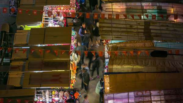 Timelapse static shot of busy Hong Kong marketplace, birds eye view at night. Rights-managed stock video