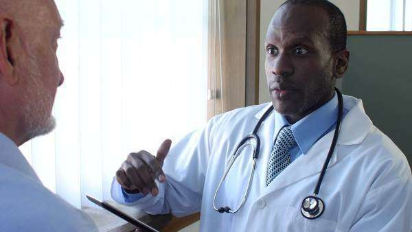 Black male doctor talking with white senior male patient stock footage