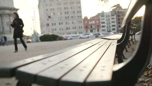 Brooklyn, New York City: Close-up of a city park bench as a woman dressed in black approaches Royalty-free stock video