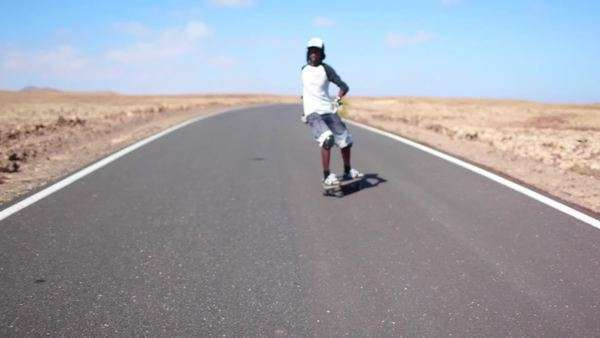 Teenaged skateboarder racing downhill on a deserted road Royalty-free stock video