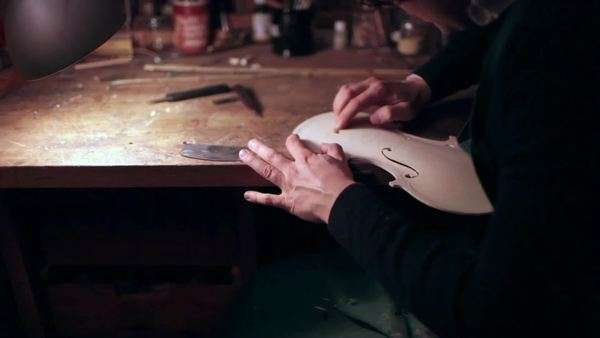 Close-up shot of a violin maker sanding the soundboard of the violin Royalty-free stock video
