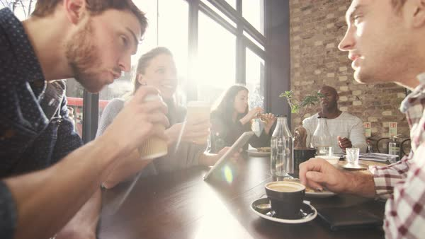 Happy group of friends chatting & having drinks in city coffee shop. Royalty-free stock video