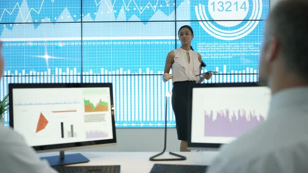 Business team in modern office, looking at video wall with graphs and data Royalty-free stock video