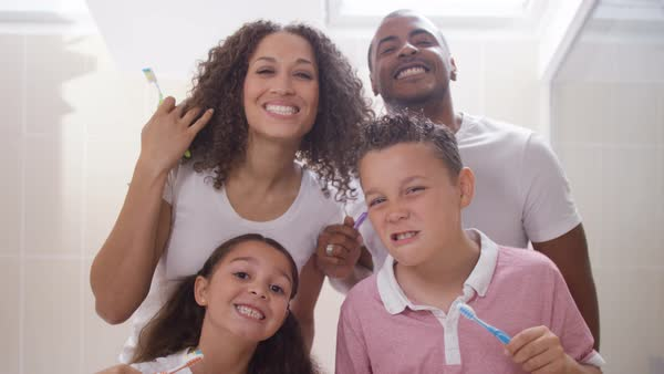 Happy mixed race family in bathroom brushing their teeth togethe  Royalty free stock video. Cute young brother   sister in bathroom  looking in mirror