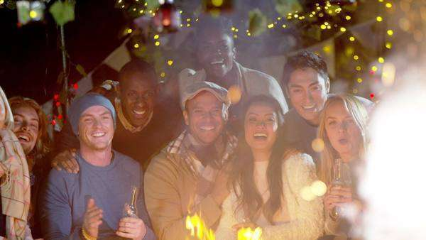 Happy friends socializing and watching fireworks outdoors in front of open fire. Royalty-free stock video