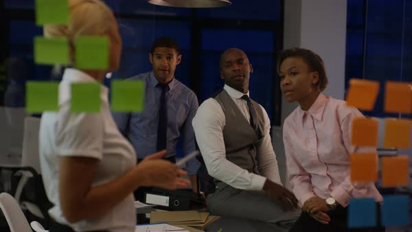 African American business team working late, brainstorming for ideas with  sticky notes  stock footage