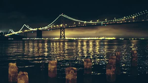 Static shot of bridge in San Fransico bay, with wooden poles sticking out of the water in foreground. Lights go in and out of focus for bokeh effect. Royalty-free stock video