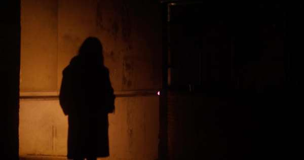 A young woman walks down a dark alleyway late at night in London Royalty-free stock video