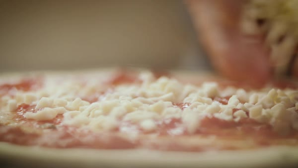 Hand-held shot of a person sprinkling cheese on a pizza Royalty-free stock video