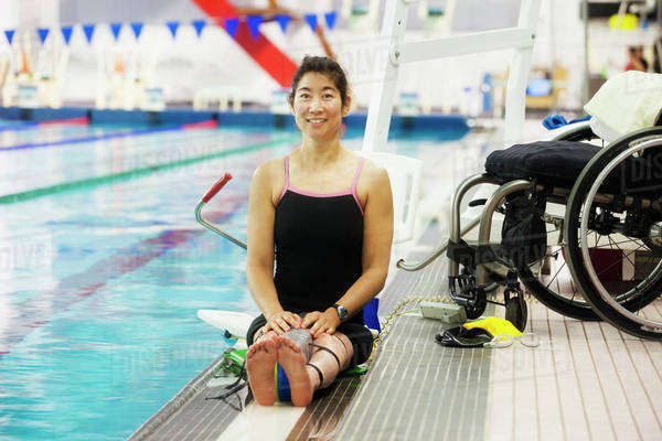 A paraplegic woman sits at the edge of a swimming pool on - Swimming pool wheelchair lift law ...
