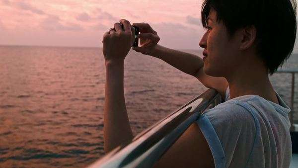 Woman on boat cruise takes photo of beautiful sunset on her mobile cell phone, creating memories Royalty-free stock video