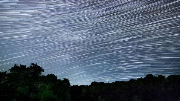 Milky Way star trails; timelapse of stars and Milky Way over a field with trees Royalty-free stock video