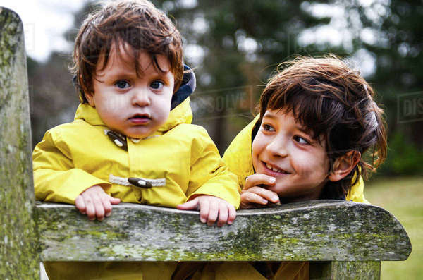 1f93f94737c9 Portrait of baby boy and big brother in yellow anoraks on park bench ...