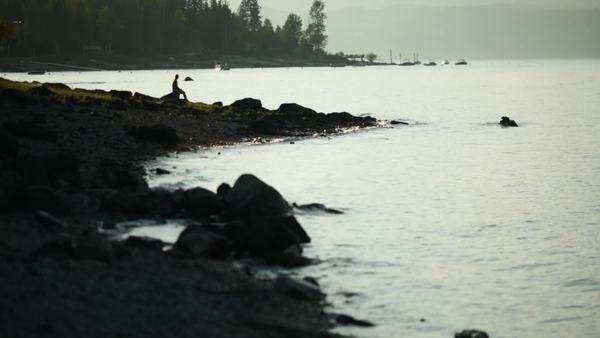 Wide shot of a woman sitting on the shore Royalty-free stock video