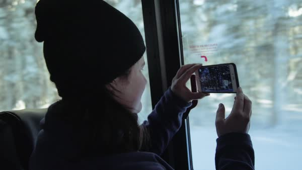 Medium close-up shot of a person filming with a smartphone on a bus Royalty-free stock video