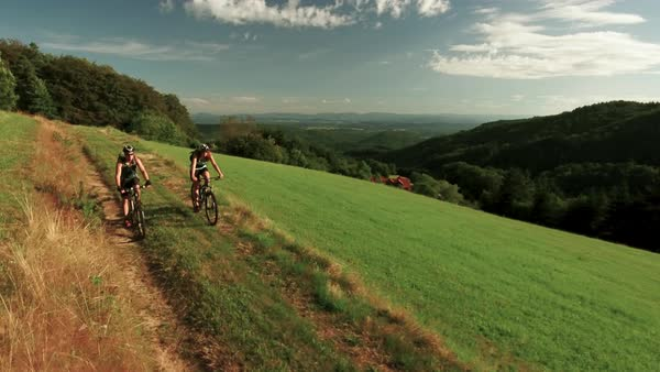 Wide shot of two cyclists riding on grassy hillside Royalty-free stock video