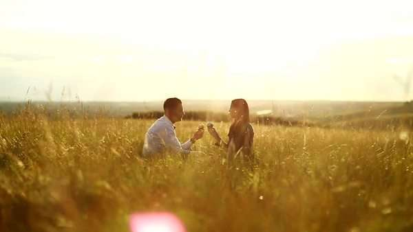 Couple sitting in the middle of a field enjoying cupcakes Royalty-free stock video